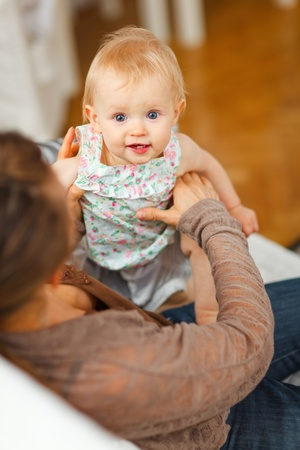 playing on divan: Portrait of cheerful baby playing on mamas knees at home