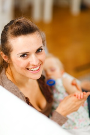 Young beautiful mother with sleeping baby on hands at home