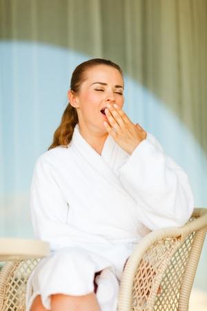 yawing: Mujer en bata de ba�o sentada en la terraza y la gui�ada Foto de archivo