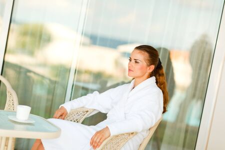 sagacious: Serious attractive female in bathrobe sitting at table on terrace with cup of coffee
