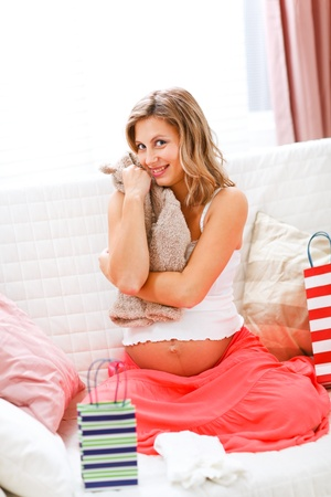 Happy pregnant woman sitting on sofa with shopping bags and hugging baby clothes  Stock Photo