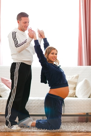 Young husband helping his pregnant wife making fitness exercise at home  photo
