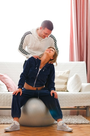 Young man helping his pregnant wife doing sport exercise at home  photo