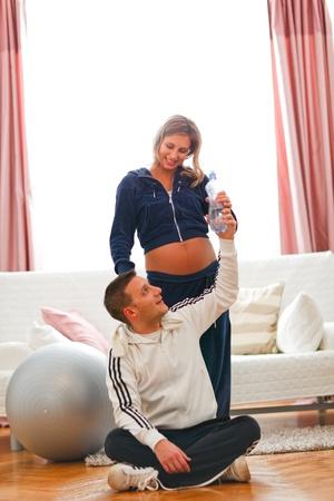 sport wear: Feliz mujer embarazada con su esposo en el deporte llevan el agua potable despu�s de fitness