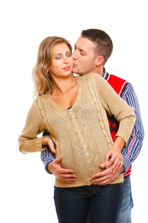 Young husband kissing his pregnant wife  on white background   photo