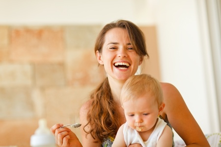 Portrait of laughing young mother feeding baby  photo