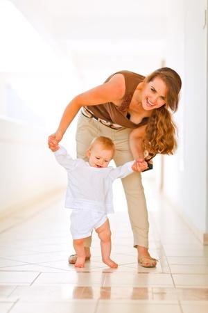 Happy mom helping baby to walk