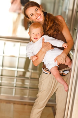 Portrait of smiling mother with baby looking out from elevator  Stock Photo