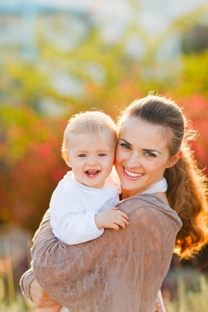 gleeful: Portrait of happy mother with smiling baby on street  Stock Photo