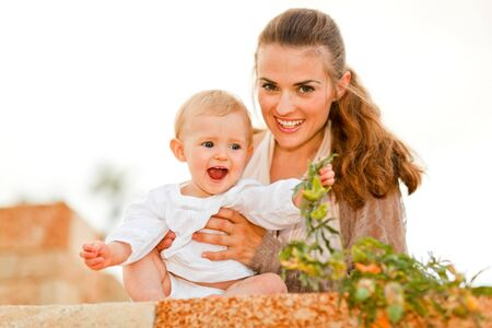 laughing baby: Portrait of happy mother and laughing baby playing with plants