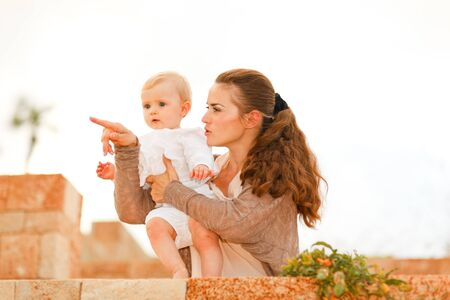 inquisitively: Mother showing something to her baby
