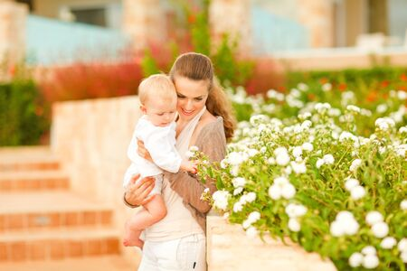 interrogatively: Caring mother showing plants to her interested baby