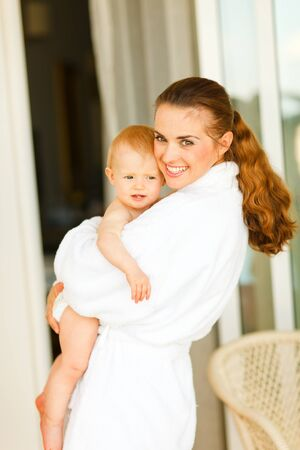 Portrait of young mother in bathrobe with baby in hand