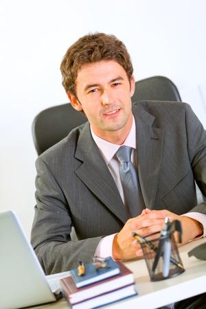 Portrait of happy modern businessman in office  photo