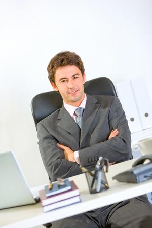 Portrait of modern businessman sitting at office desk  photo