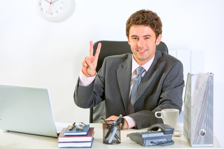 Smiling modern businessman sitting at office desk and showing victory gesture  photo