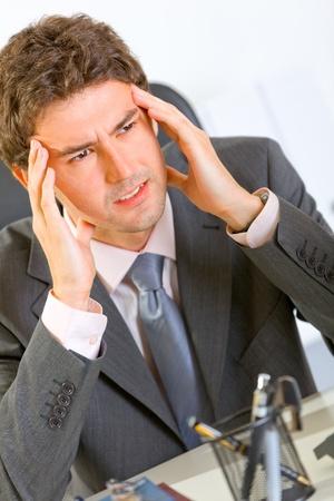 uptight: Portrait of stressed modern businessman sitting at office desk