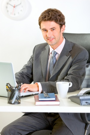 Modern businessman sitting at office desk and working on laptop  photo