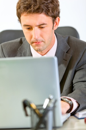 Portrait of modern businessman sitting at office desk and working on laptop  photo