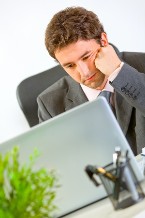 Bored modern businessman working on laptop at office   photo