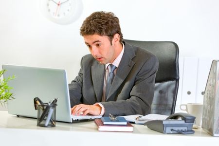 Surprised modern businessman looking in laptop at office   photo