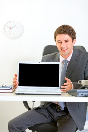 Smiling businessman sitting at office desk and showing laptops blank screen  photo