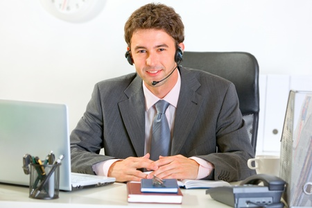 Portrait of smiling modern manager with headset  photo