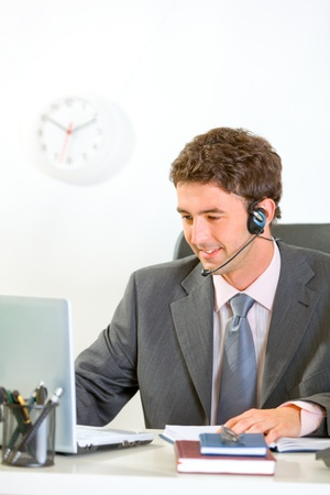 Smiling modern businessman with headset looking in laptop  photo