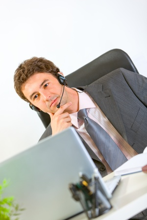Thoughtful modern businessman with headset working on laptop  photo