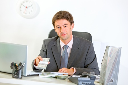 Modern businessman sitting at office desk and giving money packs  photo