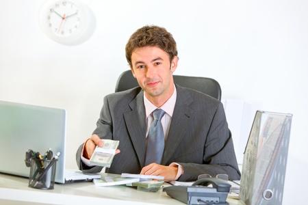 money packs: Modern businessman sitting at office desk and giving money packs