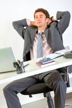 Pleased modern businessman relaxing on office armchair  photo