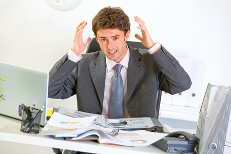 Confused modern businessman lost in documents  photo