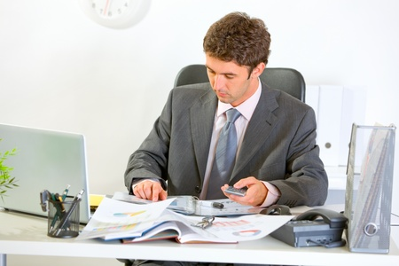 Confident modern businessman working with documents  photo