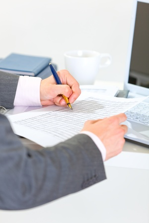 Close up on hands of businessman writing in document  photo