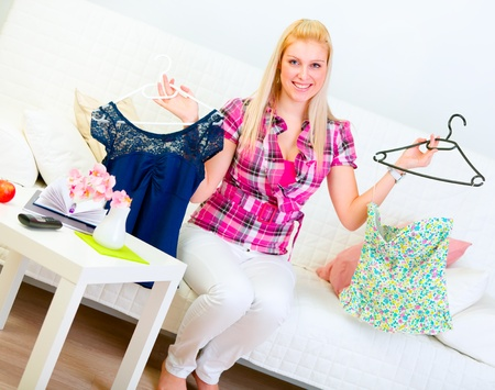 Smiling young woman sitting on sofa and choosing clothes