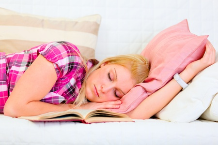 Pretty young woman sleeping on sofa with open book near head  Stock Photo