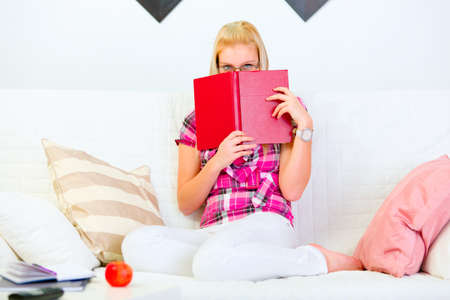 Woman sitting on sofa and hiding face behind book  photo