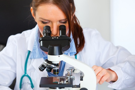 Closeup on doctor woman working with microscope in laboratory