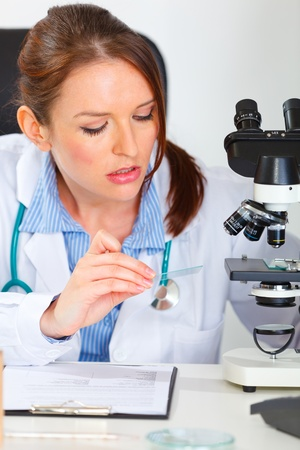 centrality: Busy female medical doctor working sample in laboratory