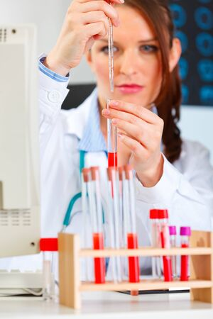 centrality: Female medical doctor working with test tube at cabinet