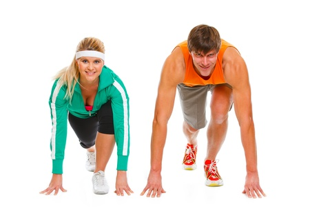 start position: Healthy young man and fit female in start position ready for run race isolated on white