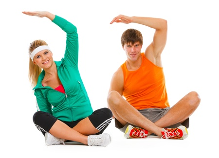 Fit young female and guy in sportswear sitting on floor and making exercises isolated on white  photo