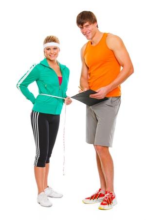 hombre escribiendo: Fitness Girl medir la cintura y el resultado por escrito en el portapapeles del hombre aislado en blanco Foto de archivo