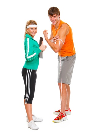 Male athlete measuring biceps and smiling girl in sportswear showing thumbs up  photo