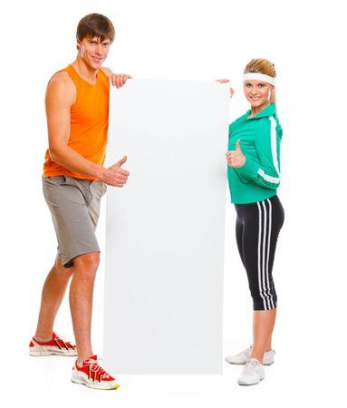 Joven mujer y el hombre en ropa deportiva con la cartelera en blanco y mostrando los pulgares para arriba Foto de archivo - 11383236