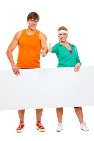 male athlete: Fitness girl and male athlete with blank billboard and showing thumbs up Stock Photo