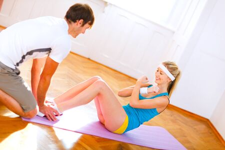 home trainer: Man helping slim girl making abdominal crunch