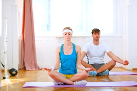 Young man and fit woman doing yoga at home  photo