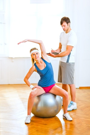 Smiling girl making exercises on fitness ball under the supervision of personal trainer   photo
